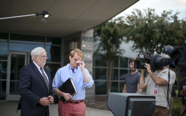Chris Hurst (R), a journalist at the station and boyfriend of killed journalist Alison Parker pauses for a moment as Jeff Marks (L), general manager for WDBJ7 looks on as they speak with NBC's Today Show outside of the offices for WDBJ7 where killed journalists Alison Parker and Adam Ward worked in Roanoke, Virginia August 27, 2015. REUTERS/Chris Keane
