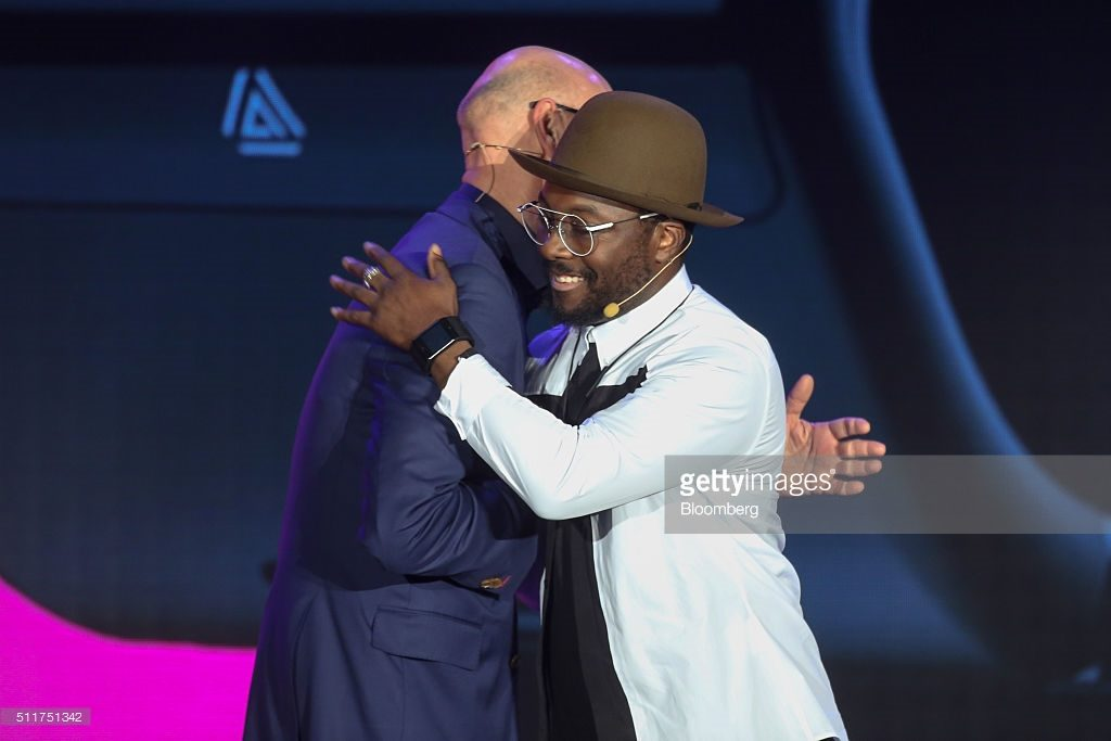 Timotheus Hoettges, chief executive officer of Deutsche Telekom AG, left, hugs Will.I.Am, musician-turned-entrepreneur, at the Telekom Unleashed event launching the Dial smartwatch at the Mobile World Congress in Barcelona, Spain, on Monday, Feb. 22, 2016. Mobile World Congress, an annual phone-industry event organized by GSMA Ltd., runs from Feb 22 to Feb 25. Photographer: Chris Ratcliffe/Bloomberg *** Local Caption *** Will.I.Am; Timotheus Hoettges